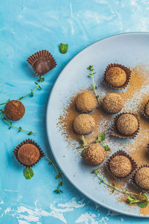 Cocoa balls, handmade chocolate balls cakes in a blue tray, sprinkled with cocoa powder, fresh mint and thyme on dark blue concrete surface background. Close up, copy space, shallow depth of the field Reklamní fotografie - 120139952