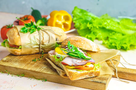 Ciabatta sandwich with ham, tomato, cheese, pepper, onion and salad on wooden cutting board with ingredients. Stock Photo
