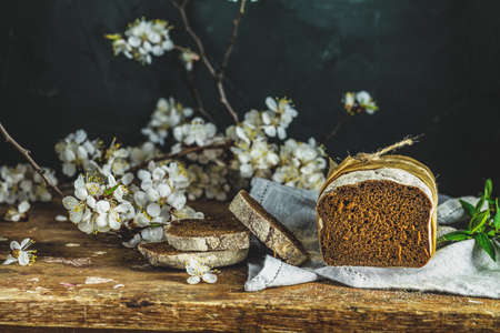 Sliced freshly baked rye handmade breads on old wooden table with linen napkin and apricot tree blossom branch. Dark rustic style. Фото со стока