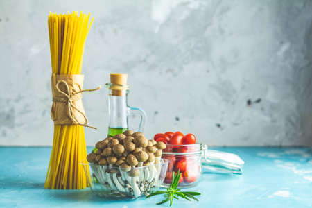 Spaghetti, shimeji mushroom, olive oil,  pink salt, empty ceramic bowl, wooden spoons for salad over blue concrete background. Healthy food concept, copy space for you text. Stock Photo