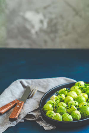 Fresh organic Brussels sprouts in served on black plate, dark blue concrete table surface, copy space for you text.