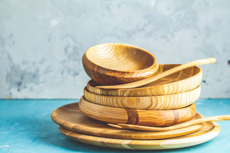 Variety of wooden bowl, wooden spoons for salad over blue texture background. Food or ecology kitchen concept. Copy space for you text.
