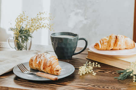 Continental traditional breakfast with croissants and coffee served on wooden table background empty copy space. French breakfast.
