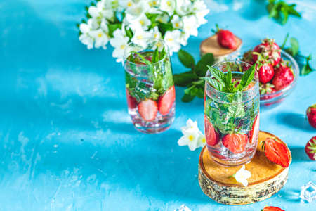 Detox infused water with strawberry and mint in highball glasses on blue concrete table background, copy space. Cold summer drink. Mineral water. Imagens