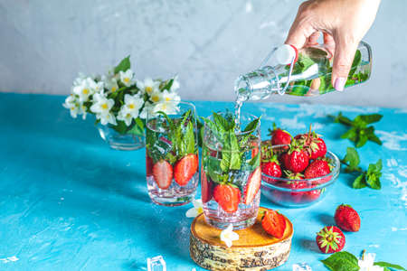 Woman pouring lemonade from bottle into glass. Detox infused water with strawberry and mint in highball glasses on blue concrete table background, copy space. Cold summer drink. Mineral water. Imagens
