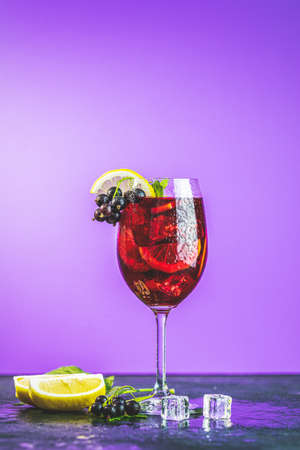 Cold red cocktail with blackcurrant, lemon, mint and ice in tall glass on violet background. Summer drinks and alcoholic cocktails. Alcoholic cocktail Blackcurrant mojito