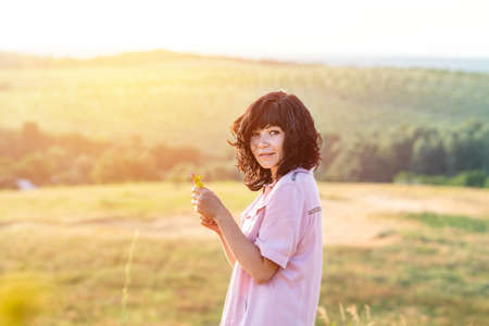 Cute happy romantic beautiful female brunette on the summer green hills landscape at sunset time, close up, shallow depth of the field Stock Photo - 126343720