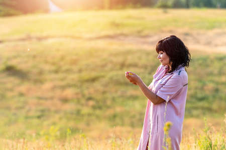 Cute happy romantic beautiful female brunette on the summer green hills landscape at sunset time, close up, shallow depth of the field Stock Photo - 126343723