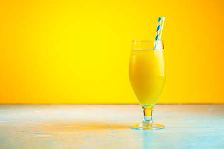 Glass of pineapple tropical fresh juice on yellow background. Summer drinks and alcoholic cocktails. Stock Photo - 126343722