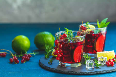 Cold red cocktail with currant, lime, mint, thyme and ice in glass on dark concrete surface table. Summer drinks and alcoholic cocktails. Alcoholic cocktail Currant mojito. Stock Photo - 126343728