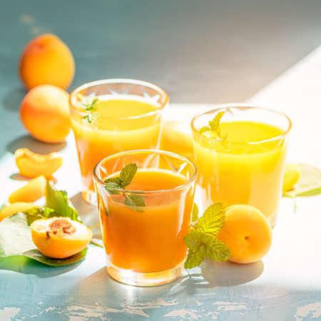 Glass of fresh healthy apricot or peach smoothie or juice on light blue concrete surface table. Sunny light. Shallow depth of the field, close up, copy space for you text Stock Photo - 126343735