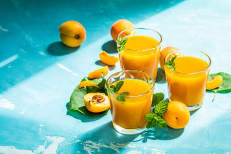Glass of fresh healthy apricot or peach smoothie or juice on light blue concrete surface table. Sunny light. Shallow depth of the field, close up, copy space for you text Stock Photo - 126343736