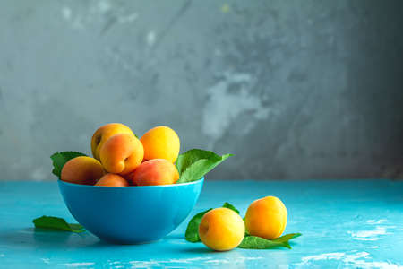 Fresh sweet orange apricots in blue bowl on the blue concrete surface table, selective focus, shallow depth of the fields Stock Photo - 126343741