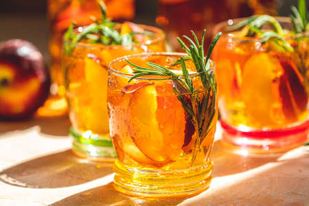 Glasses with drops of sweet peach iced tea, Summer cold peach fizz cocktail with rosemary. Sunny light. Shallow depth of the field, close up, copy space for you text Stock Photo - 126343739