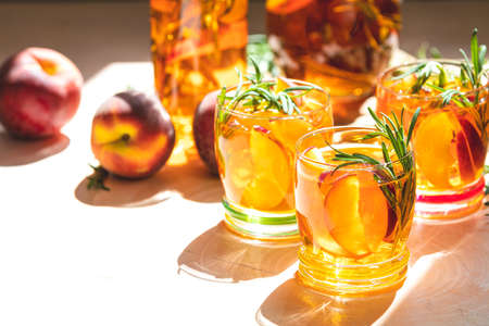 Glasses of sweet peach iced tea, Summer cold peach fizz cocktail with rosemary. Sunny light. Shallow depth of the field, close up, copy space for you text Stock Photo - 126343738
