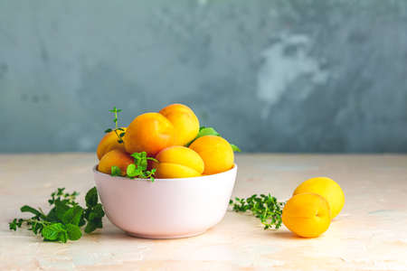 Fresh sweet orange apricots in pink bowl on the pink concrete surface table, selective focus, shallow depth of the fields Stock Photo - 126343743