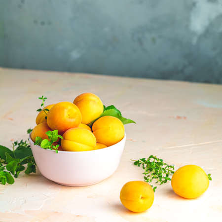 Fresh sweet orange apricots in pink bowl on the pink concrete surface table, selective focus, shallow depth of the fields Stock Photo - 126343745