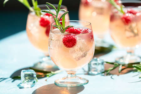 Pink drink with ice. Close up mix berries ice soda with thyme in a transparent glass on white table at cafe.Summer cold Welcome drink and cocktail. Holiday, sunny light Stock Photo - 128015621