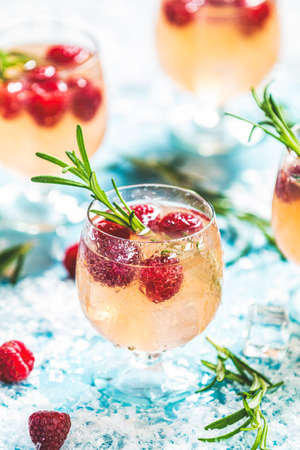 Christmas pink drink raspberry with rosemary and ice. Glasses with cold and healthy beverage. Welcome drink. Holiday, sunny light Stock Photo - 128015623