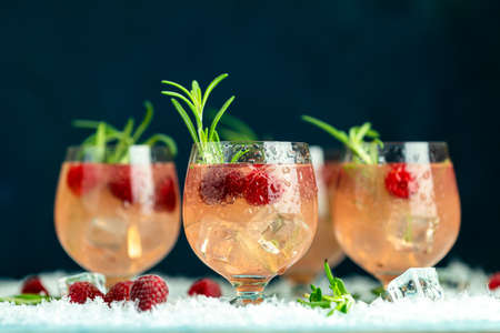 Fresh raspberry cocktail with rosemary and ice in glasses with water drops on dark blue background. Christmas and New Year holiday welcome drink. Stock Photo - 128015628