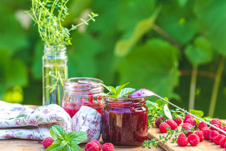 Raspberry jam and fresh raspberry on a rustic wooden table outdoors. Sunny day, green leaves background Stock Photo - 128015638