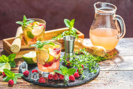 Refreshing mint cocktail mojito with rum, lime and raspberry, cold drink or beverage Stock Photo - 128015649
