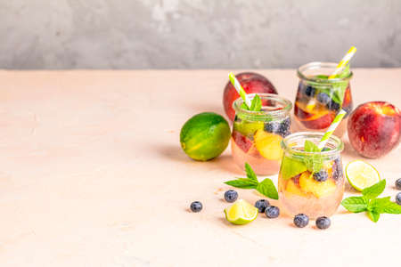 Blueberry and peach infused water, cocktail, lemonade or tea. Summer iced cold drink with blueberry, lime, peach and mint. Stock Photo - 128302331