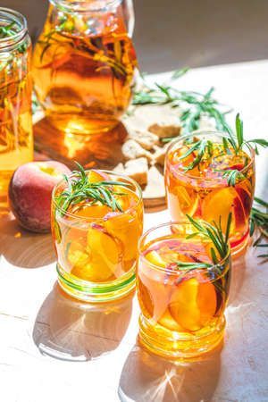 Glasses of sweet peach iced tea, Summer cold peach fizz cocktail with rosemary. Stock Photo - 128302328