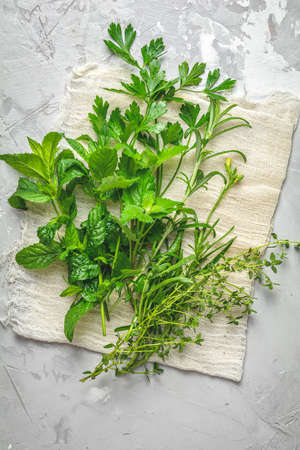 Herbs and spices. Fresh herbs selection included rosemary, thyme, mint, lemon balm, parsley and arugula. Overhead view, copy space. Stock Photo - 128302352