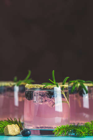 Fresh blueberry cocktail with rosemary and ice in glasses with decorate brown sugar on turquoise surface and black background. Christmas and New Year holiday welcome drink. Stock Photo - 128302354