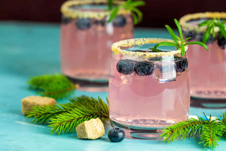 Fresh blueberry cocktail with rosemary and ice in glasses with decorate brown sugar on turquoise surface and black background. Christmas and New Year holiday welcome drink. Stock Photo - 128302374
