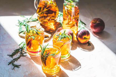 Glasses of sweet peach iced tea, Summer cold peach fizz cocktail with rosemary. Sunny light. Фото со стока