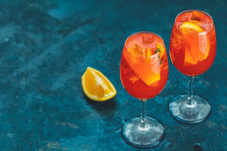 Cocktail aperol spritz in big wine glass with water drops on dark blue background. Summer Italian fresh alcohol cold drink. Stock Photo - 128302424
