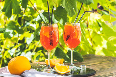 cocktail in big wine glass with oranges, summer Italian fresh alcohol cold drink. Sunny garden with vineyard background Фото со стока - 128302469