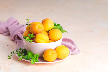 Fresh sweet orange apricots in pink bowl on the pink concrete surface table, selective focus, shallow depth of the fields Stock Photo - 128302523