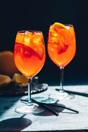 cocktail in big wine glass with oranges, summer Italian fresh alcohol cold drink. Dark bar counter background with tools, summer mood concept, selective focus Stock Photo - 128302557