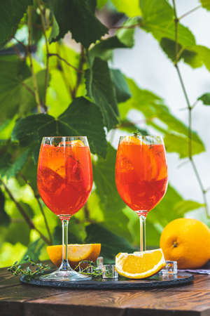 cocktail in big wine glass with oranges, summer Italian fresh alcohol cold drink. Sunny garden with vineyard background, summer mood concept, selective focus Stock Photo - 128302613