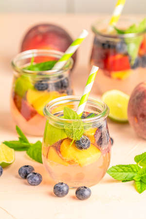 Blueberry and peach infused water, cocktail, lemonade or tea. Summer iced cold drink with blueberry, lime, peach and mint. Stock Photo - 128302656