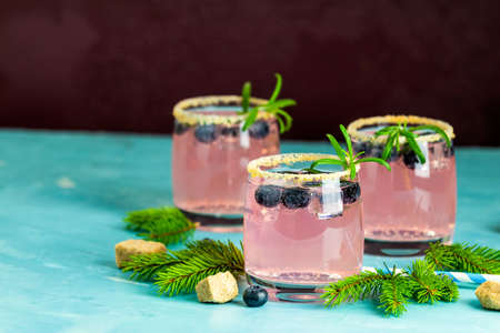 Fresh blueberry cocktail with rosemary and ice in glasses with decorate brown sugar on turquoise surface and black background. Stock Photo - 128302878