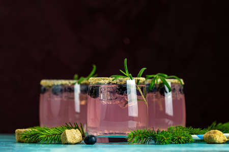 Fresh blueberry cocktail with rosemary and ice in glasses with decorate brown sugar on turquoise surface and black background. Stock Photo - 128302882