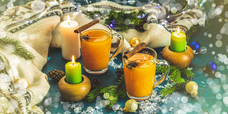 Christmas and New Year banner composition. Two cup of hot spicy tea with sea buckthorn, cinnamon and star anise, branches of pine and spruce,  candles and holiday decor, bokeh, dark background. Stock Photo - 128861747