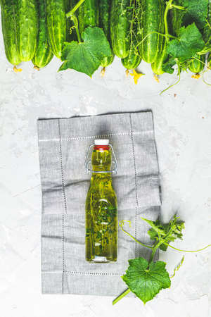 Bottle of olive oil with thyme on linen cloth with green fresh cucumbers with leaves and branches over gray texture background. Stock Photo - 128861189