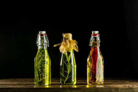 Different sorts of cooking oil, Assortment of sunflower, corn, olives oils with herbs and spices in different bottles on dark background Stock Photo - 128861437