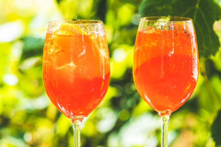 cocktail in big wine glass with oranges, summer Italian fresh alcohol cold drink. Sunny garden with vineyard background, summer mood concept, selective focus Stock Photo - 129689249