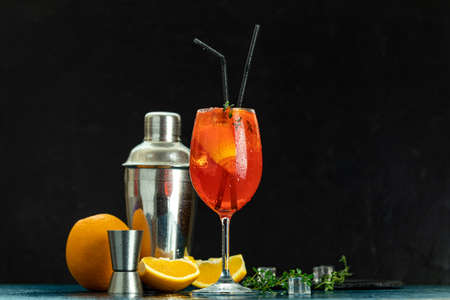 Cocktail  in big wine glass with water drops on dark background. Summer alcohol cocktail with orange slices. Stock Photo - 129770149
