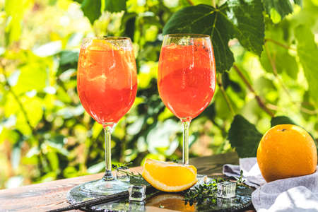 Two Aperol in big wine glass with oranges, summer Italian fresh alcohol cold drink. Sunny garden with vineyard background, summer mood concept, selective focus Stock Photo - 129770170