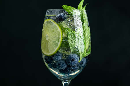 Summer alcoholic cocktail blueberry mojito with rum, mint, lime and ice, close up, dark background, selective focus, copy space Stock Photo - 129770224