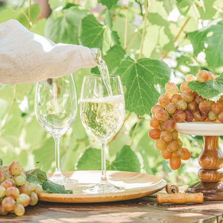 Pouring wine in glass. Green grape and white wine in vineyard. Sunny garden with vineyard background, summer mood concept, selective focus Stock Photo - 129770379