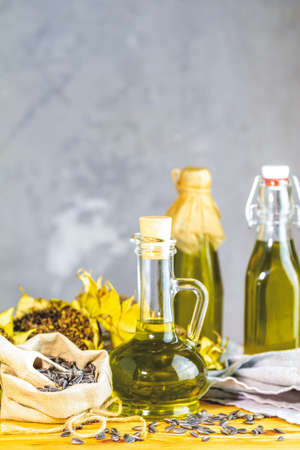 Various types of oil in bottles, dried sunflowers and seeds on wooden table. Close up, copy space. Stock Photo - 129770386