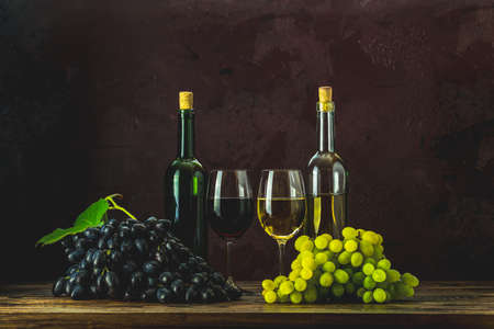 Glasses and bottles of wine and grapes on dark claret bordeaux concrete surface background Stock Photo - 129770391